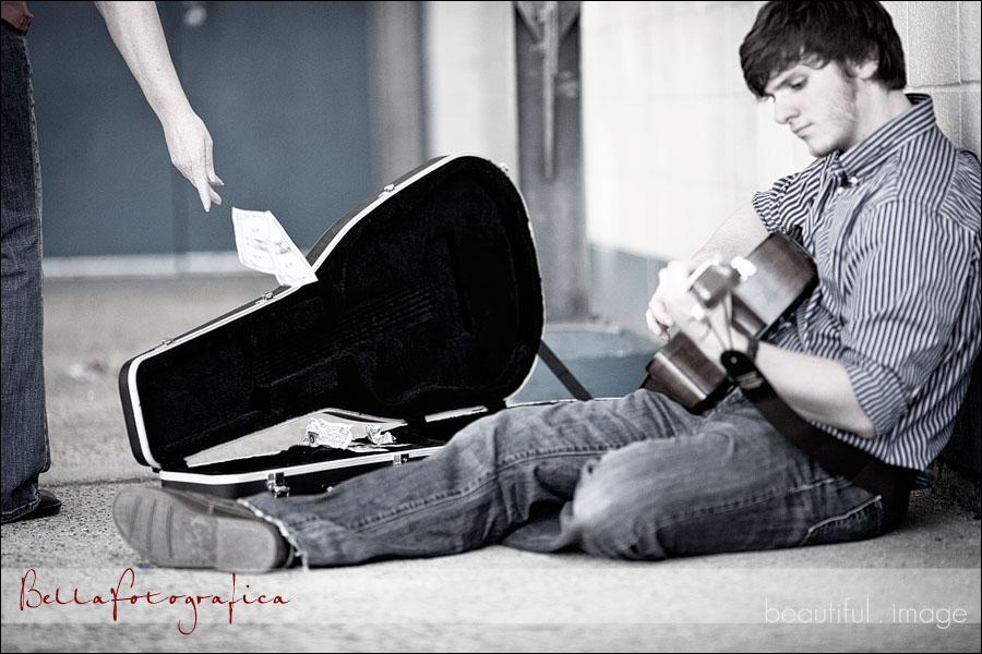 senior playing his guitar making money