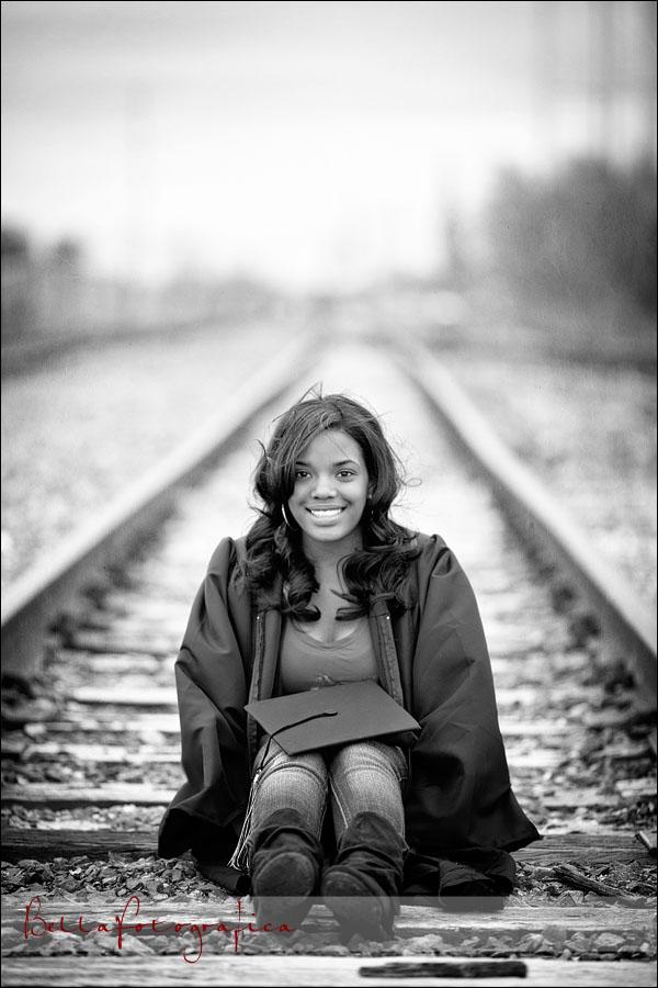 high school senior sitting on railroad tracks