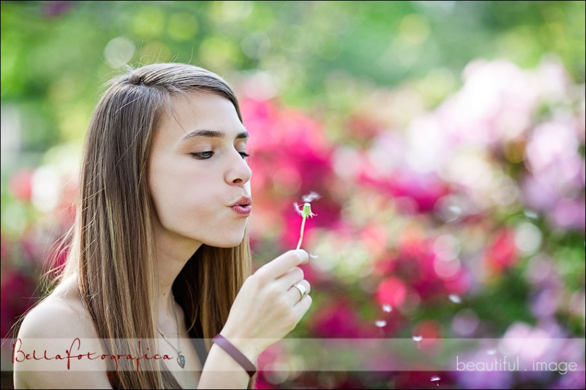 senior girl blowing on dandelion