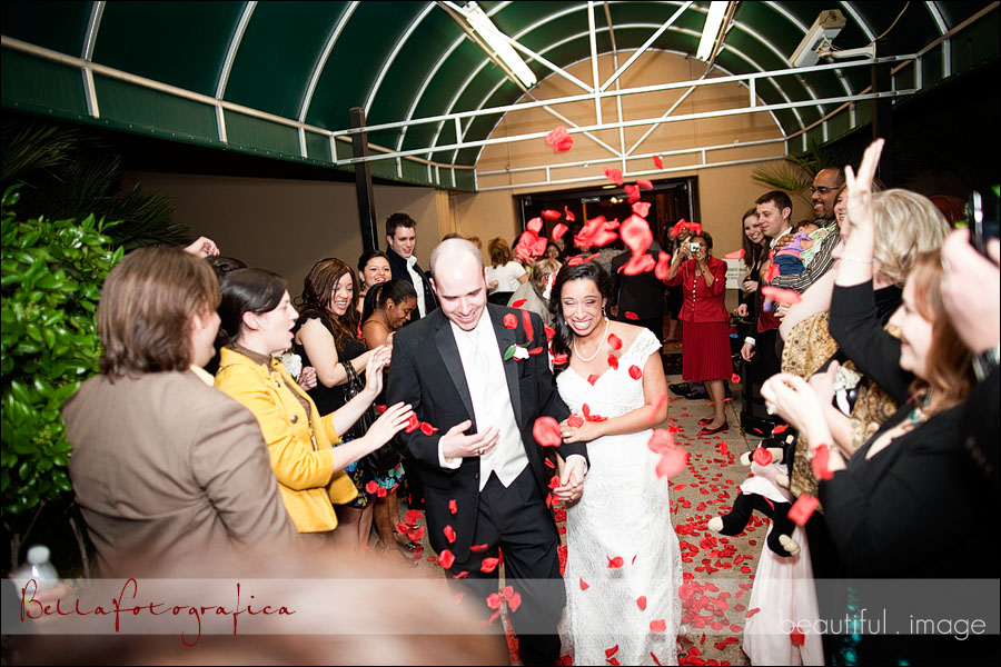 bride and groom leaving under rose petals