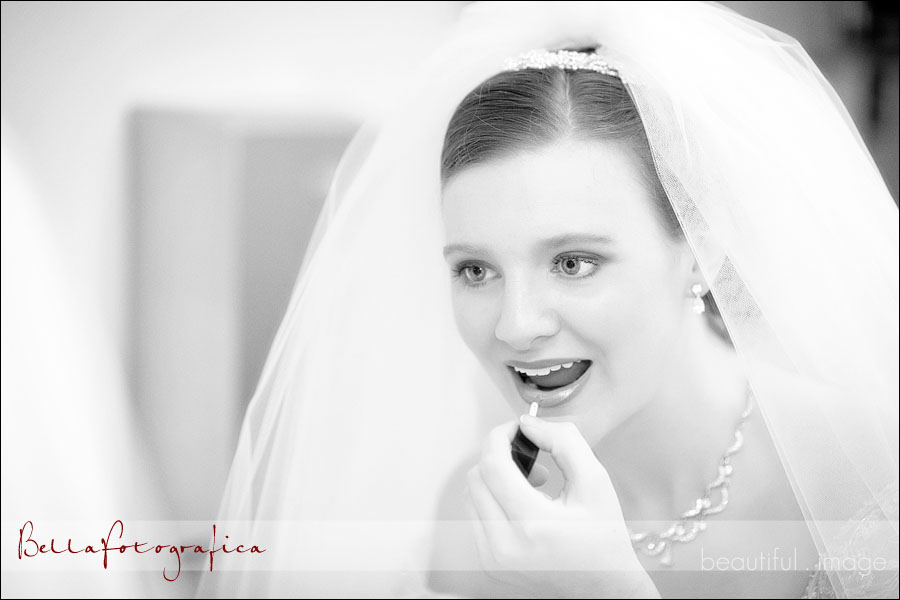 bride touching up her lipstick