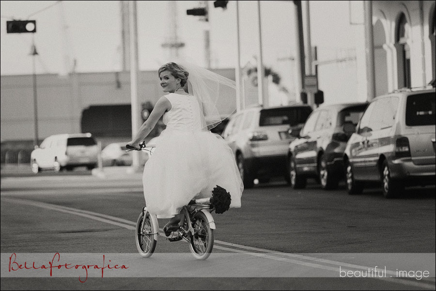 bride riding a bike on the strand