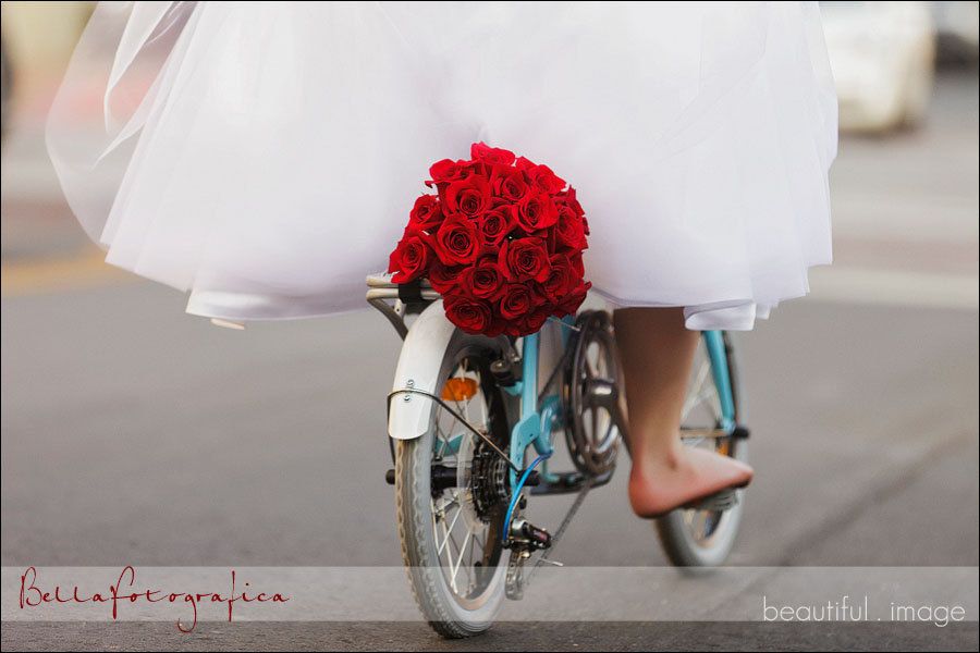 brides red rose bouquet strapped to her bike
