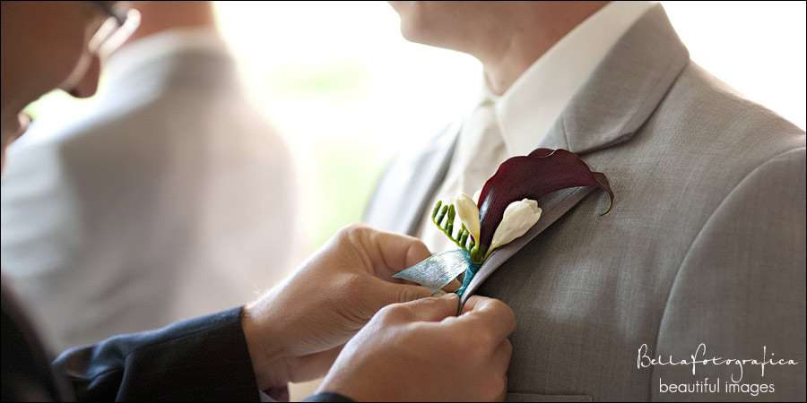 groom getting bouttoniere pinned on
