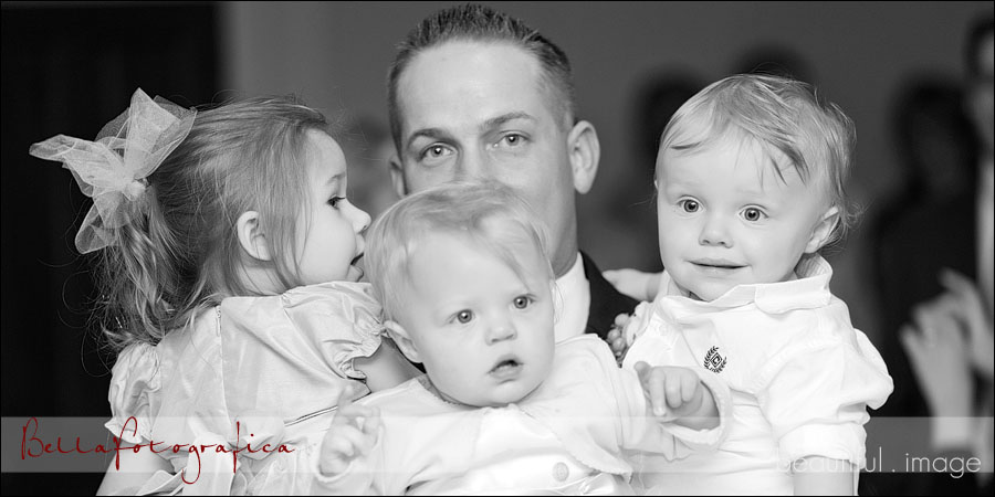groom holding three toddlers